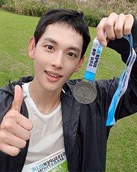 Им Ши Ван гордо позирует с медалью участника